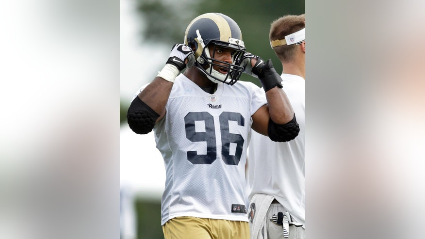 St. Louis Rams defensive end Michael Sam straps on his helmet during training camp at the NFL football team's practice facility Saturday, July 26, 2014, in St. Louis. (AP Photo/Jeff Roberson)
