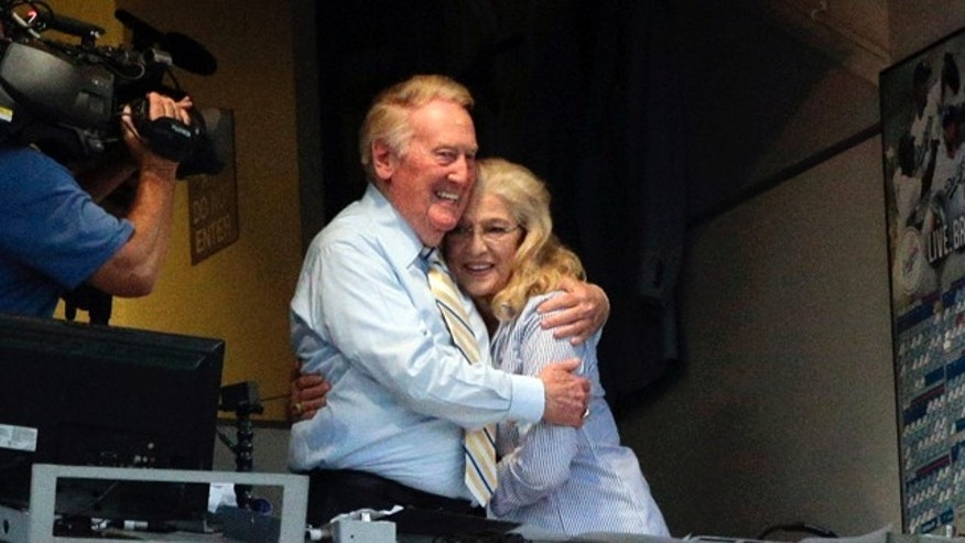 July 29, 2014: Broadcaster Vin Scully, left, embraces his wife, Sandi, at Dodger Stadium during a baseball game between the Los Angeles Dodgers and the Atlanta Braves in Los Angeles. The Dodgers announced that Scully will remain with the team for the 2015 season. (AP Photo/Jae C. Hong)
