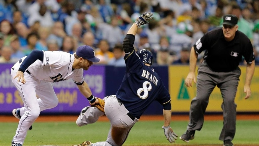 Tampa Bay Rays third baseman Evan Longoria, left, tags out Milwaukee Brewers' Ryan Braun at third base on a stolen base attempt during the third inning of an interleague baseball game Wednesday, July 30, 2014, in St. Petersburg, Fla. Making the call is umpire Bill Welke, right. (AP Photo/Chris O'Meara)