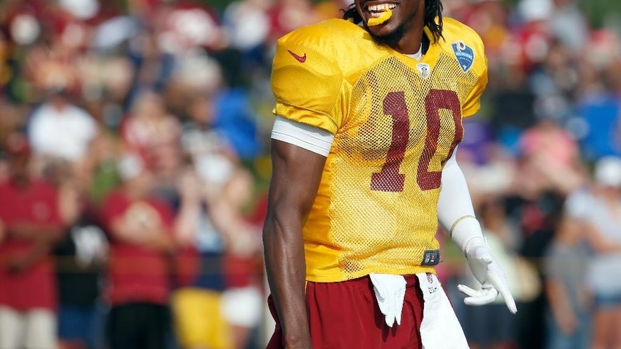 Washington Redskins quarterback Robert Griffin III smiles at the fans during practice at the team's NFL football training facility, Saturday, July 26, 2014 in Richmond, Va. (AP Photo)