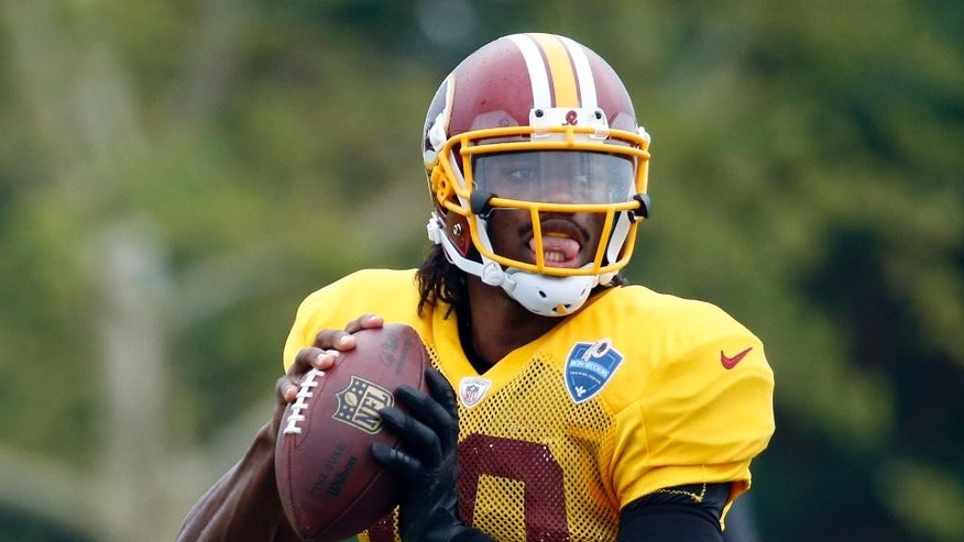 Washington Redskins quarterback Robert Griffin III looks to pass during practice at the team's NFL football training facility, Sunday, July 27, 2014 in Richmond, Va. (AP Photo/Alex Brandon)