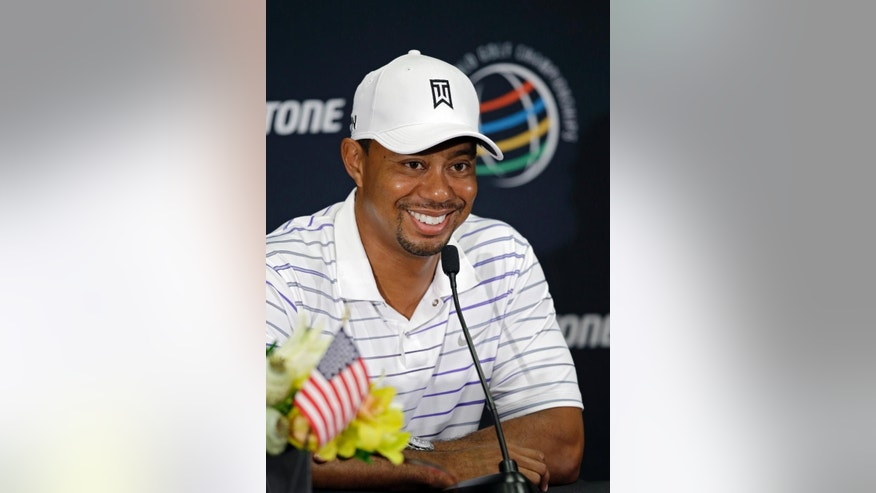 Tiger Woods smiles at a question during his news conference during the final practice day for the Bridgestone Invitational golf tournament Wednesday, July 30, 2014, in Akron, Ohio. (AP Photo/Mark Duncan)