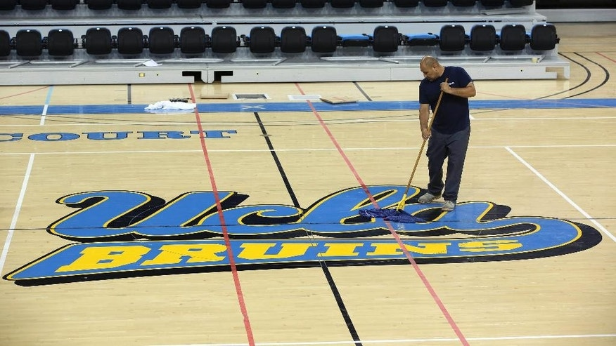 Worker Ruben Monter mops up the floor at Pauley Pavillion Wednesday July 30, 2014 in Los Angeles. A ruptured 93-year-old water main on Tuesday left the UCLA campus awash in 8 million gallons of water in the middle of California's worst drought in decades, stranding people in parking garages and flooding the school's storied basketball court less than two years after a major renovation.  (AP Photo/ Nick Ut)