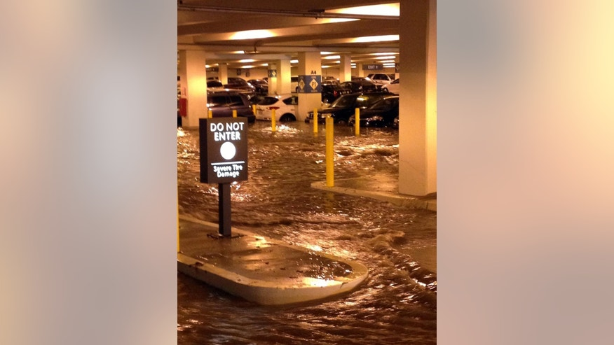 In this Tuesday, July 29, 2014 photo, water flows into a parking structure at UCLA after a ruptured 93-year-old, 30-inch water main left the Los Angeles campus awash in 8 million gallons of water in the middle of California's worst drought in decades. The water also flooded the school's storied basketball court, which underwent a major renovation less than two years ago. (AP Photo/Anuj Dixit)