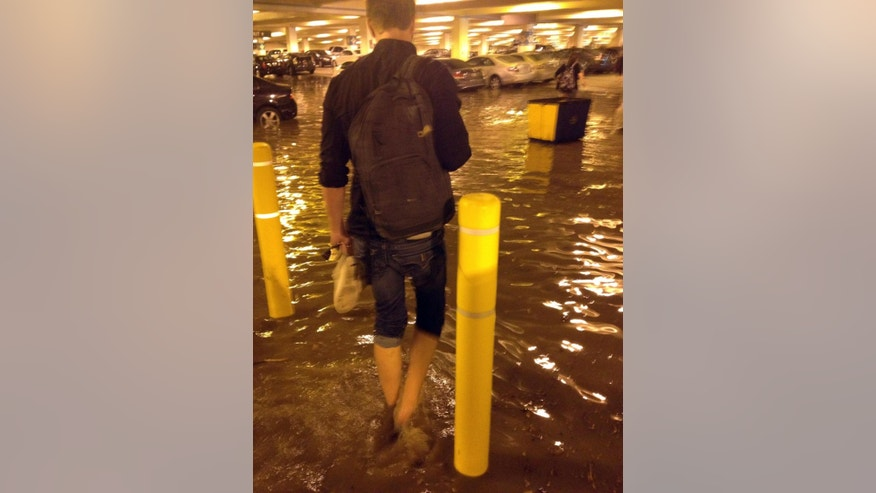 In this Tuesday, July 29, 2014 photo, a person walks through a flooded parking structure at UCLA after a ruptured 93-year-old, 30-inch water main left the Los Angeles campus awash in 8 million gallons of water in the middle of California's worst drought in decades. The water also flooded the school's storied basketball court, which underwent a major renovation less than two years ago. (AP Photo/Anuj Dixit)