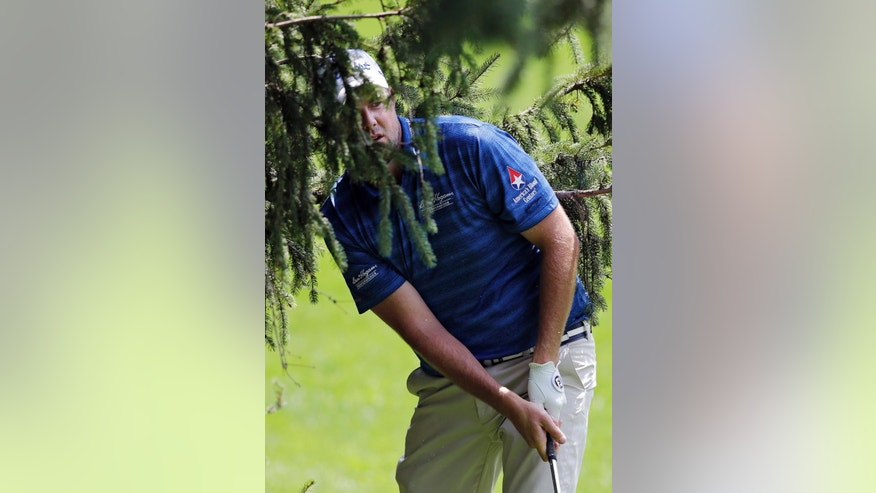 Marc Leishman, from Australia, hits from a tree to the 18th green during the first round of the Bridgestone Invitational golf tournament Thursday, July 31, 2014, at Firestone Country Club in Akron, Ohio. (AP Photo/Mark Duncan)