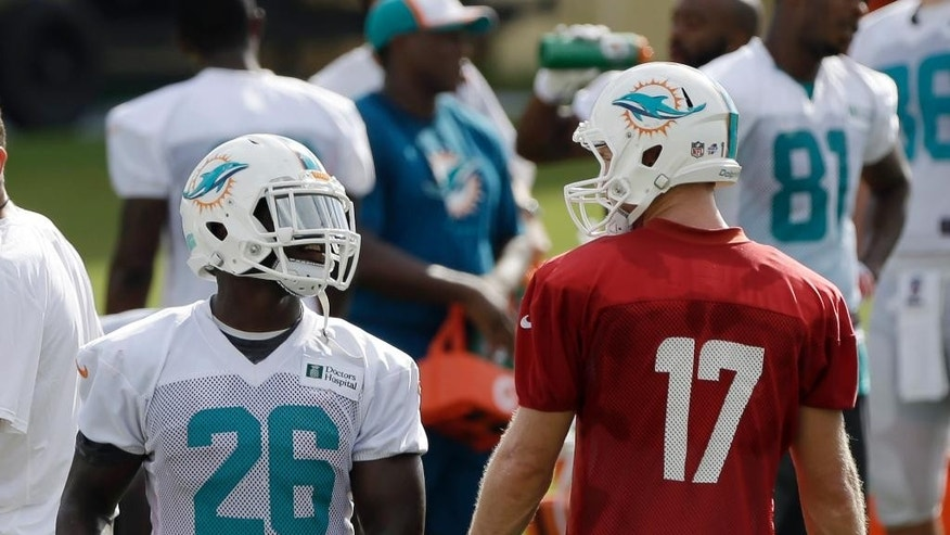 Miami Dolphins running back Lamar Miller (26) talks to quarterback Ryan Tannehill (17) during NFL football training camp in Davie, Fla., Wednesday, July 30, 2014. (AP Photo/Alan Diaz)