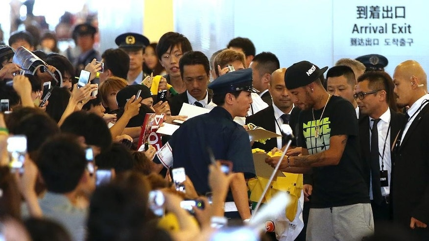 Brazilian soccer player Neymar greets his fans upon arrival at Haneda airport in Tokyo, Thursday, July 31, 2014. Neymar is in Tokyo for several promotional events. (AP Photo/Eugene Hoshiko)
