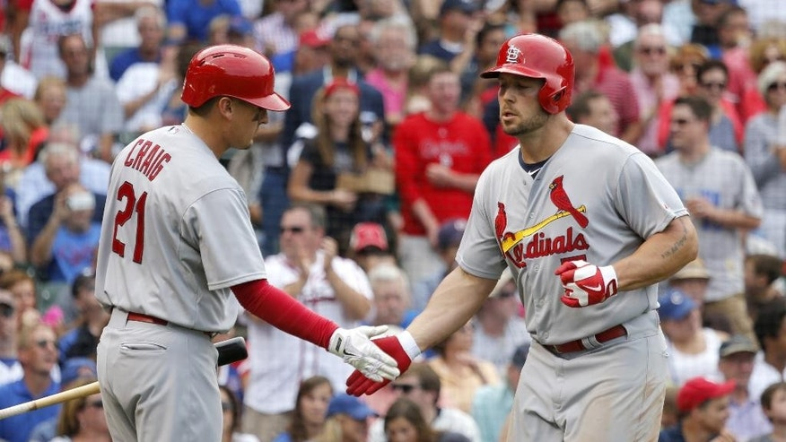 St. Louis Cardinals' Allen Craig (21) greets Matt Holliday outside the dugout after Holliday's home run off Chicago Cubs starting pitcher Travis Wood during the fifth inning of a baseball game Friday, July 25, 2014, in Chicago. (AP Photo/Charles Rex Arbogast)