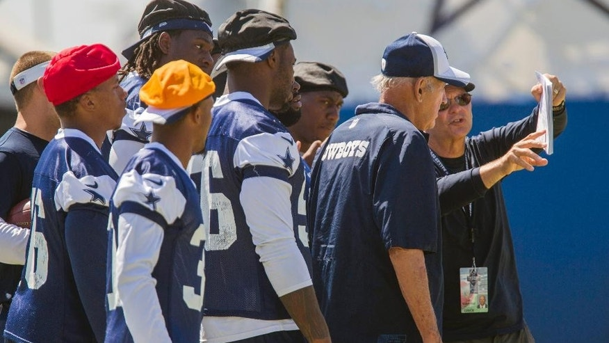 Dallas Cowboys defensive coordinator Rod Marinelli, right, shows instructions to the team during NFL football training camp, Thursday, July 31, 2014, in Oxnard, Calif. (AP Photo/Ringo H.W. Chiu)