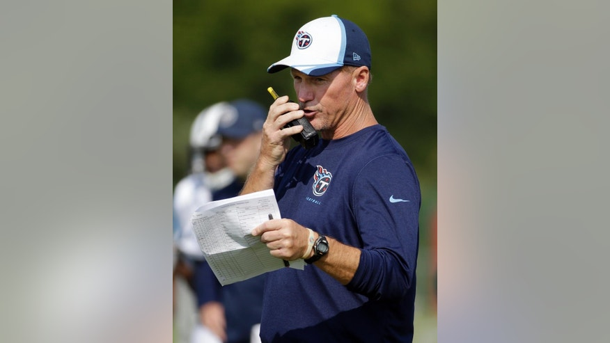 Tennessee Titans head coach Ken Whisenhunt talks on a walkie-talkie during NFL football training camp Tuesday, July 29, 2014, in Nashville, Tenn. (AP Photo/Mark Humphrey)