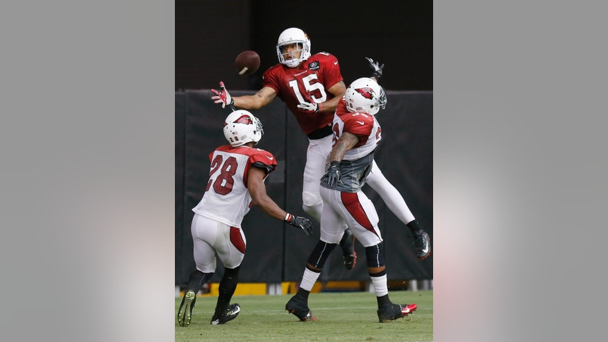 Arizona Cardinals' Justin Bethel (28) and Deone Buccanon (36) break up a pass intended for Michael Floyd (15) during NFL football training camp practice on Wednesday, July 30, 2014, in Glendale, Ariz. (AP Photo/Ross D. Franklin)