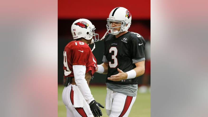 Arizona Cardinals quarterback Carson Palmer (3) talks with receiver Ted Ginn (19) after a play during NFL football training camp practice on Wednesday, July 30, 2014, in Glendale, Ariz. (AP Photo/Ross D. Franklin)