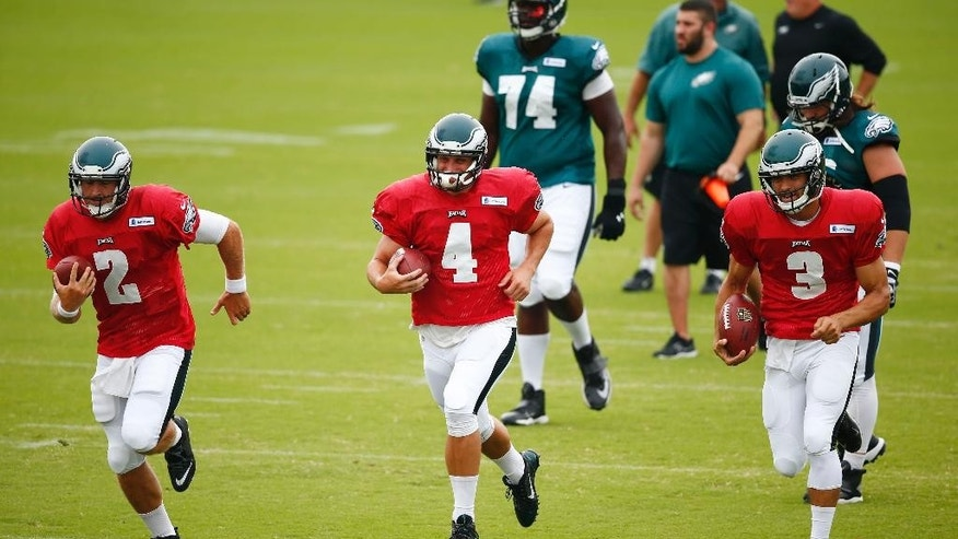 Philadelphia Eagles quarterback Matt Barkley, left, G.J. Kinne, Mark Sanchez (3) run a drill during NFL football training camp Friday, Aug. 1, 2014, in Philadelphia. (AP Photo/Matt Rourke)