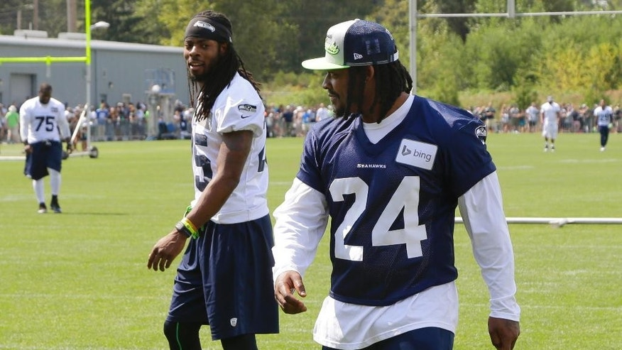 Seattle Seahawks running back Marshawn Lynch, right, and cornerback Richard Sherman, left, walk off the field following NFL Football training camp, Friday, Aug. 1, 2014, in Renton, Wash. Friday was Lynch's first day attending training camp after staying away due to contract issues. (AP Photo/Ted S. Warren)