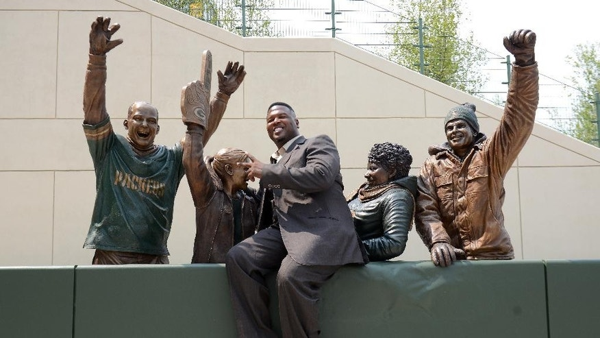 LeRoy Butler, credited with originating the Lambeau Leap, is the first to pose with the piece during the unveiling of the Lambeau Leap sculpture on Harlan Plaza at Lambeau Field, Friday, August 1, 2014 in Green Bay, Wis.  (AP Photo/The Green Bay Press-Gazette, Jim Matthews) NO SALES
