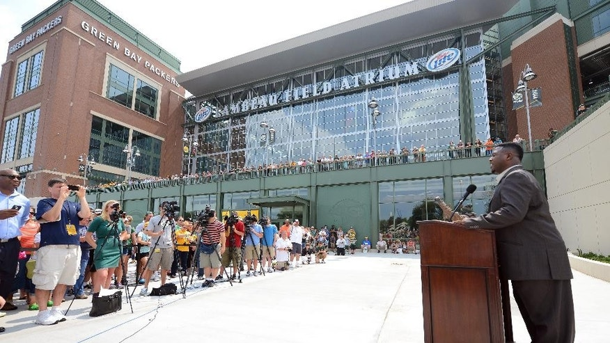 LeRoy Butler, credited with originating the Lambeau Leap, right, talks about the fans' love for the Packers during the unveiling of the Lambeau Leap sculpture on Harlan Plaza at Lambeau Field, Friday, August 1, 2014 in Green Bay, Wis.  (AP Photo/The Green Bay Press-Gazette, Jim Matthews) NO SALES