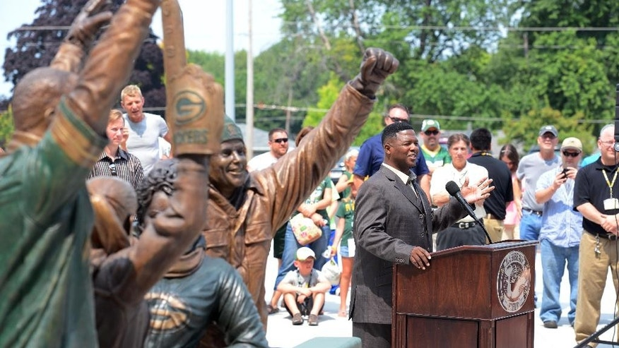 LeRoy Butler, right, credited with originating the Lambeau Leap,  talks about the fans' love for the Packers during the unveiling of the Lambeau Leap sculpture,  left, on Harlan Plaza at Lambeau Field, Friday, Aug. 1, 2014 in Green Bay, Wis.  (AP Photo/The Green Bay Press-Gazette, Jim Matthews) NO SALES
