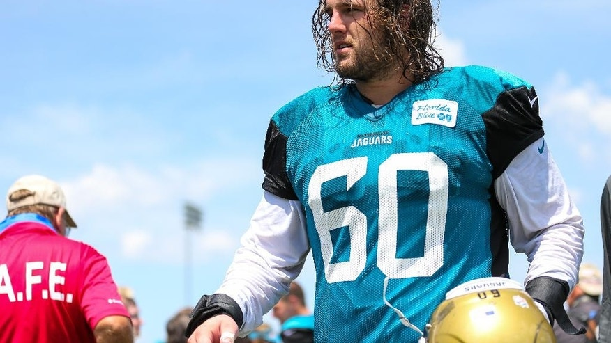 Jacksonville Jaguars center Mike Brewster (60) leaves the field following NFL football training camp in Jacksonville, Fla.,Wednesday, July 30, 2014. (AP Photo/Gary McCullough)