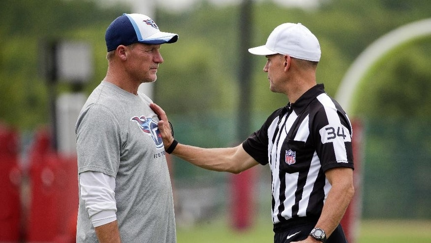 An official talks with Tennessee Titans head coach Ken Whisenhunt about how players may block during a practice at a NFL football training camp Friday, Aug. 1, 2014, in Nashville, Tenn. (AP Photo/Mark Humphrey)