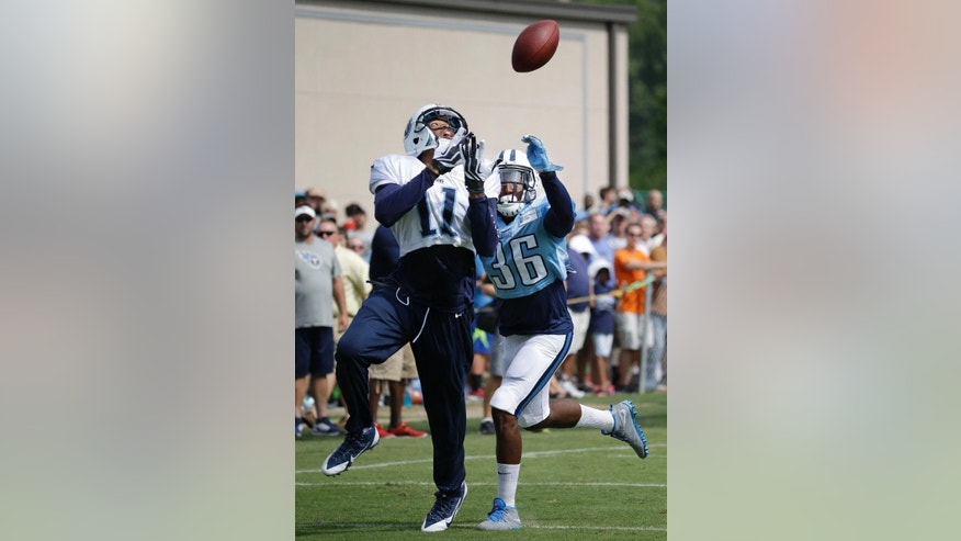 Tennessee Titans wide receiver Isaiah Williams (11) catches a pass as he is defended by cornerback Khalid Wooten (36) during NFL football training camp Friday, Aug. 1, 2014, in Nashville, Tenn. (AP Photo/Mark Humphrey)