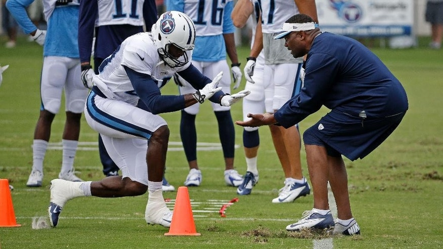 Tennessee Titans wide receiver Derek Hagan slaps hands with wide receivers coach Shawn Jefferson, right, as Hagan runs a drill during NFL football training camp Friday, Aug. 1, 2014, in Nashville, Tenn. (AP Photo/Mark Humphrey)