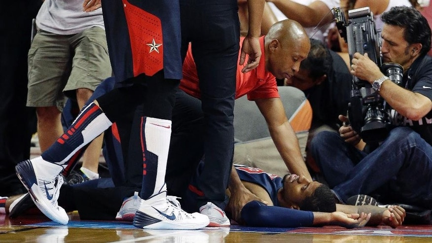 Indiana Pacers' Paul George lies on the court after he was injured during the USA Basketball Showcase game Friday, Aug. 1, 2014, in Las Vegas. (AP Photo/John Locher)
