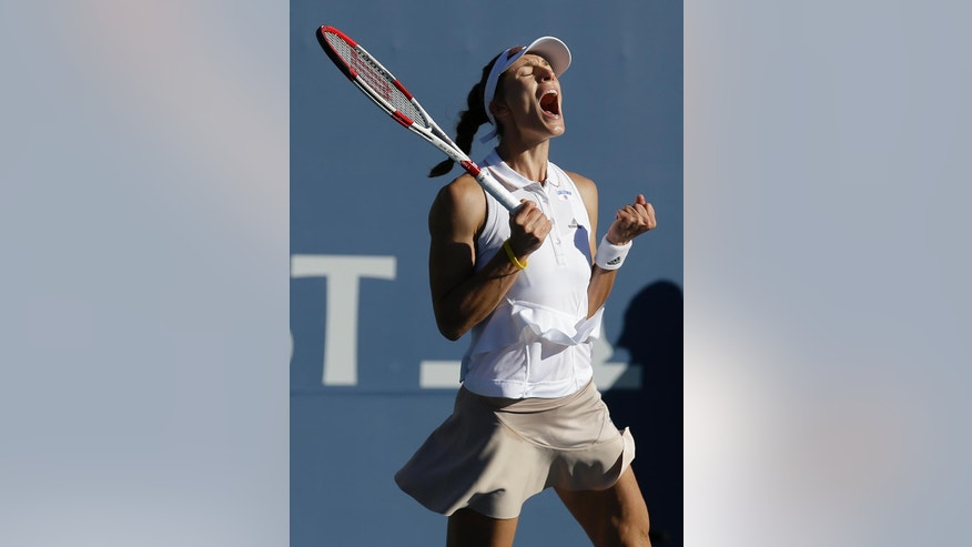 Andrea Petkovic, from Germany, celebrates after defeating Venus Williams, of the United States, at the Bank of the West Classic tennis tournament in Stanford, Calif., Friday, Aug. 1, 2014. Petkovic won 6-1, 3-6, 7-5. (AP Photo/Jeff Chiu)