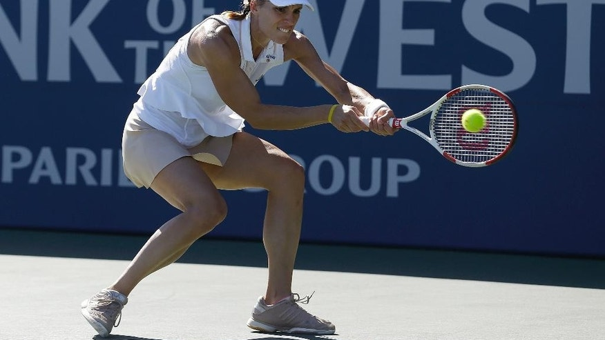 Andrea Petkovic, from Germany, returns the ball to Venus Williams, of the United States, during the second set of their match in the Bank of the West Classic tennis tournament in Stanford, Calif., Friday, Aug. 1, 2014. Petkovic won 6-1, 3-6, 7-5. (AP Photo/Jeff Chiu)
