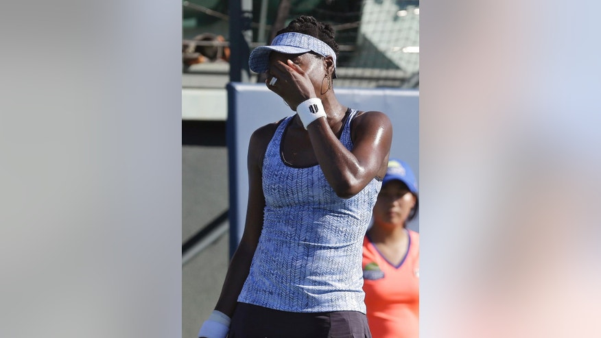 Venus Williams, of the United States, reacts after losing a point to Andrea Petkovic, from Germany, during the third set of their match in the Bank of the West Classic tennis tournament in Stanford, Calif., Friday, Aug. 1, 2014. Petkovic won 6-1, 3-6, 7-5. (AP Photo/Jeff Chiu)