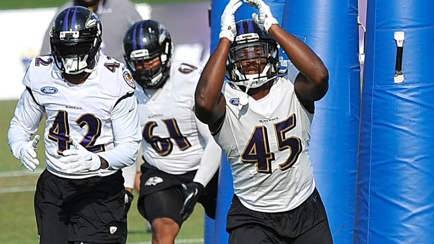 Baltimore Ravens defensive players, left to right, Dominique Franks, Levi Brown and Zachary Orr run a drill during NFL football training camp practice, Thursday, July 31, 2014, in Owings Mills, Md.(AP Photo/Gail Burton)