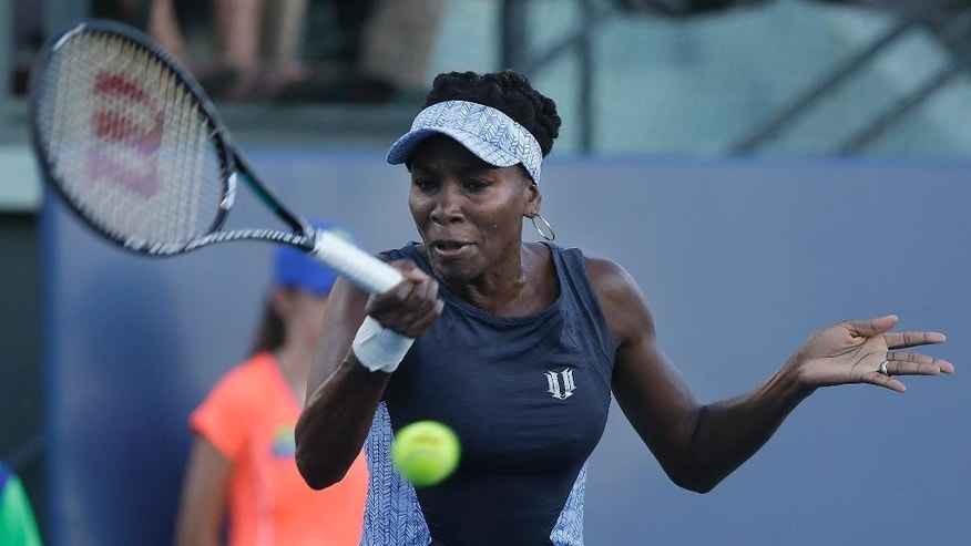Venus Williams returns the ball to Victoria Azarenka, from Belarus, during the first set of their match in the Bank of the West Classic tennis tournament in Stanford, Calif., Thursday, July 31, 2014. (AP Photo/Jeff Chiu)