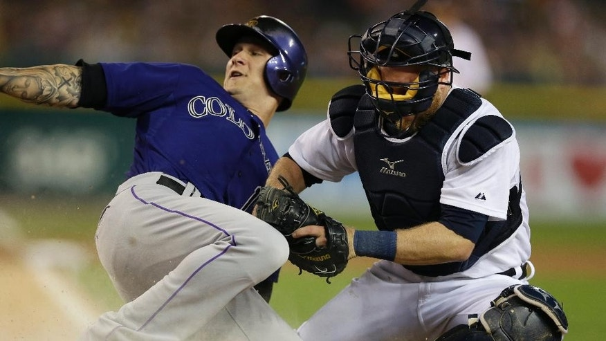 Colorado Rockies' Brandon Barnes safely slides under the tag of Detroit Tigers catcher Bryan Holaday during the seventh inning of an interleague baseball game, Friday, Aug. 1, 2014, in Detroit. (AP Photo/Carlos Osorio)