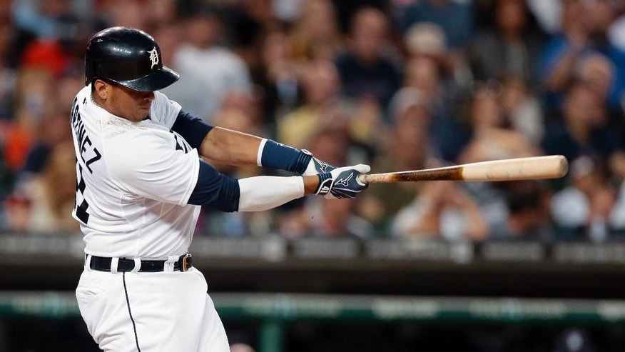 Detroit Tigers designated hitter Victor Martinez connects for a three-run home run during the fifth inning of an interleague baseball game against the Colorado Rockies, Saturday, Aug. 2, 2014, in Detroit. (AP Photo/Carlos Osorio)