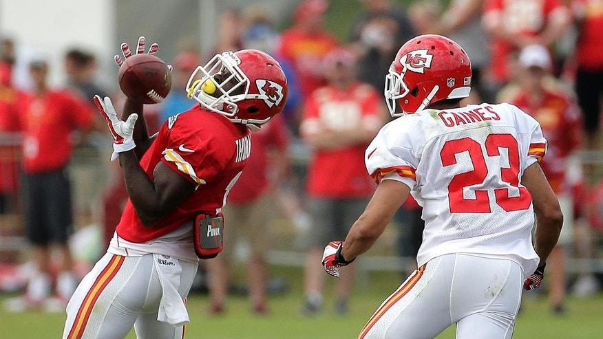 Kansas City Chiefs running back De'Anthony Thomas (1) catches a pass under pressure from cornerback Phillip Gaines (23) during NFL football training camp Friday, Aug. 1, 2014, in St. Joseph, Mo. (AP Photo/Charlie Riedel)