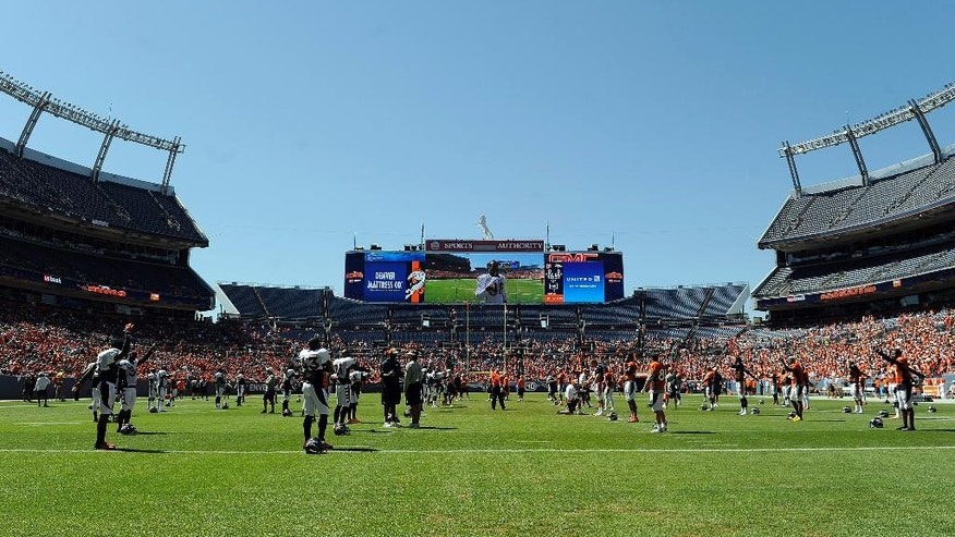Denver Broncos players stretch at NFL training camp at Sports Authority Field at Mile High on Saturday, Aug. 2, 2014, in Denver. (AP Photo/Chris Schneider)