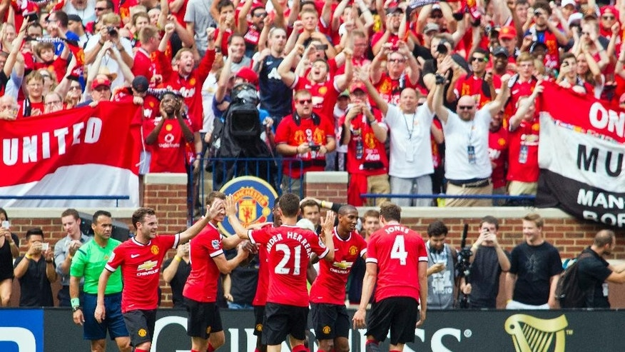 Manchester United midfielder Ashley Young, second from right, celebrates his goal against Real Madrid with teammates in the first half of a Guinness International Champions Cup soccer match at Michigan Stadium, Saturday, Aug. 2, 2014, in Ann Arbor, Mich. (AP Photo/Tony Ding)