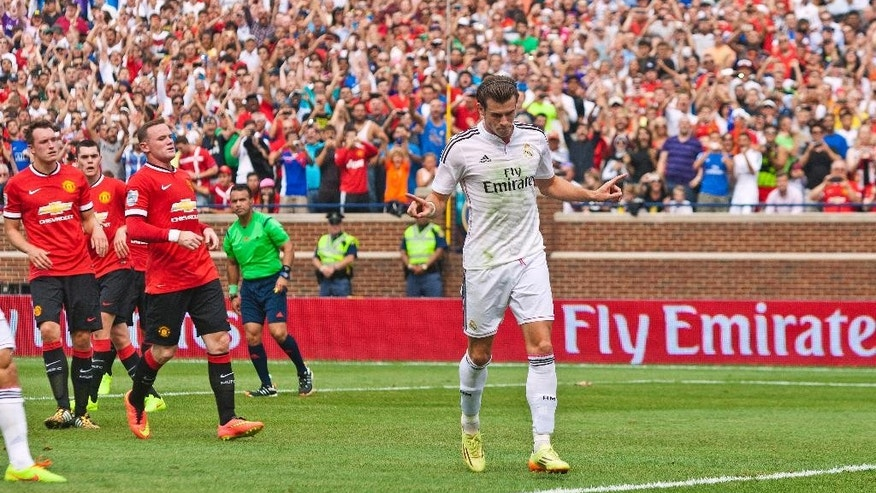 Real Madrid forward Gareth Bale, center, celebrates his penalty kick goal scored in the first half of a Guinness International Champions Cup soccer match with Manchester United at Michigan Stadium, Saturday, Aug. 2, 2014, in Ann Arbor, Mich. (AP Photo/Tony Ding)