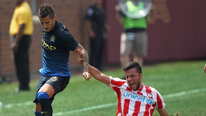 Manchester City forward Stevan Jovetic (35), left, takes the ball from Olympiacos forward Kevin Mirallas (14) in the first half of the Guinness International Champions Cup at TCF Bank Stadium on the University of Minnesota campus in Minneapolis, Saturday, Aug. 2, 2014.(AP Photo/Andy Clayton-King)