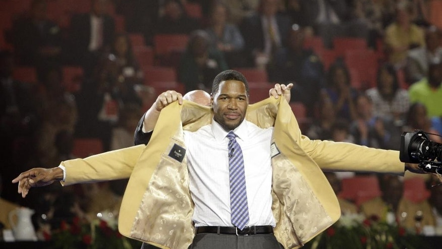 Michael Strahan has his gold jacket put on by his presenter Jay Glazer Friday, Aug. 1, 2014 during the Pro Football Hall of Fame Enshrinees' Dinner in Canton, Ohio. The induction ceremony will take place Saturday in Canton's Fawcett Stadium (AP Photo / The Repository, Bob Rossiter)