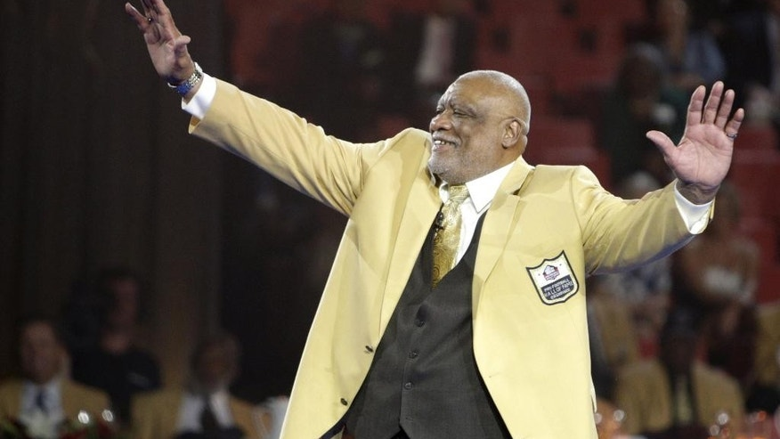 Claude Humphrey waves to the audience Friday, Aug. 1, 2014 after receiving his gold jacket during the Pro Football Hall of Fame Enshrinees' Dinner in Canton, Ohio. The induction ceremony will take place Saturday in Canton's Fawcett Stadium (AP Photo / The Repository, Bob Rossiter)