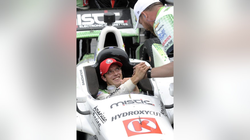 Sebastian Bourdais, of France, is congratulated by a team member after winning the pole position for Sunday's IndyCar Honda Indy 200 auto race at Mid-Ohio Sports Car Course in Lexington, Ohio, Saturday, Aug. 2, 2014. (AP Photo/Tom E. Puskar)