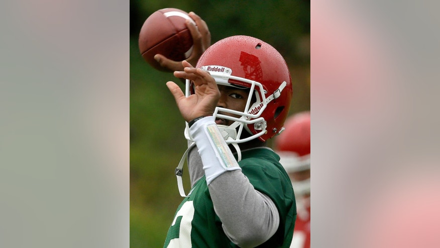North Carolina State quarterback Jacoby Brissett looks to pass during the team's first NCAA college football practice of the season in Raleigh, N.C., Saturday, Aug. 2, 2014. (AP Photo/Gerry Broome)