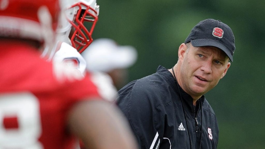 North Carolina State coach Dave Doeren watches his players during the team's first NCAA college football practice of the season in Raleigh, N.C., Saturday, Aug. 2, 2014. (AP Photo/Gerry Broome)