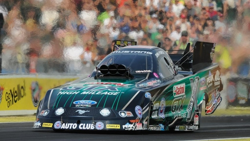 In this photo provided by NHRA, John Force drives in Funny Car qualifying Saturday, Aug. 2, 2014, at the O'Reilly Auto Parts NHRA Northwest Nationals drag races at Pacific Raceways in Kent, Wash. Force took the top spot with a run of 4.057 seconds at 308.07 mph. (AP Photo/NHRA, Jerry Foss)