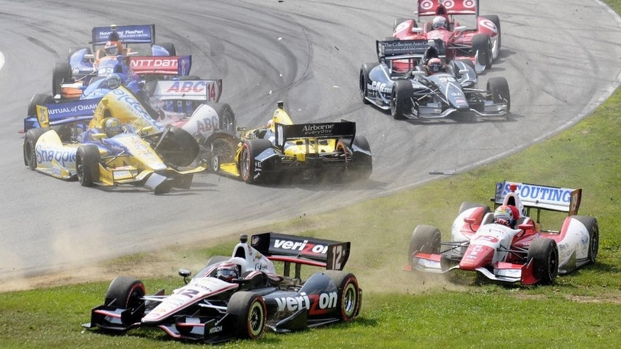 Marco Andretti, center left in the Snapple car,  collides with Tony Kanaan, of Brazil,  facing backwards, in a first lap crash during the IndyCar Honda Indy 200 auto racing at Mid-Ohio Sports Car Course in Lexington, Ohio Sunday, Aug. 3, 2014. Forced onto the grass are Will Power (12) and Justin Wilson (19). (AP Photo/Tom E. Puskar)