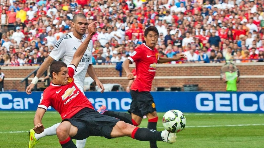 Manchester United forward Javier Hernández, front, attempts a shot on goal, with Real Madrid defender Pepe, back left, and Manchester United midfielder Shinji Kagawa, right, in the second half of a Guinness International Champions Cup soccer match at Michigan Stadium, Saturday, Aug. 2, 2014, in Ann Arbor, Mich. Manchester United won 3-1. (AP Photo/Tony Ding)