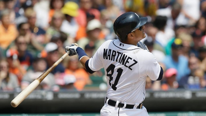Detroit Tigers designated hitter Victor Martinez watches the flight of his three-run home run during the third inning of an interleague baseball game against the Colorado Rockies, Sunday, Aug. 3, 2014, in Detroit. (AP Photo/Carlos Osorio)