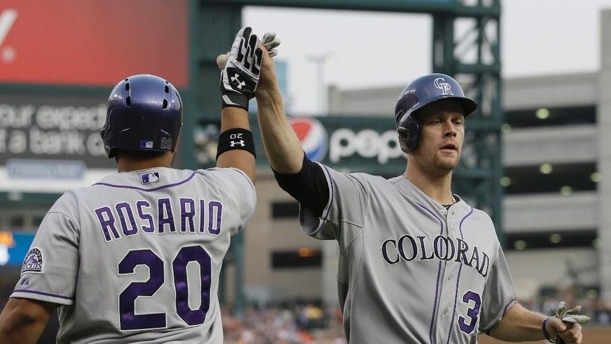 Colorado Rockies first baseman Justin Morneau, right, is congratulated by teammate Wilin Rosario after scoring during the second inning of an interleague baseball game against the Detroit Tigers, Saturday, Aug. 2, 2014, in Detroit. (AP Photo/Carlos Osorio)