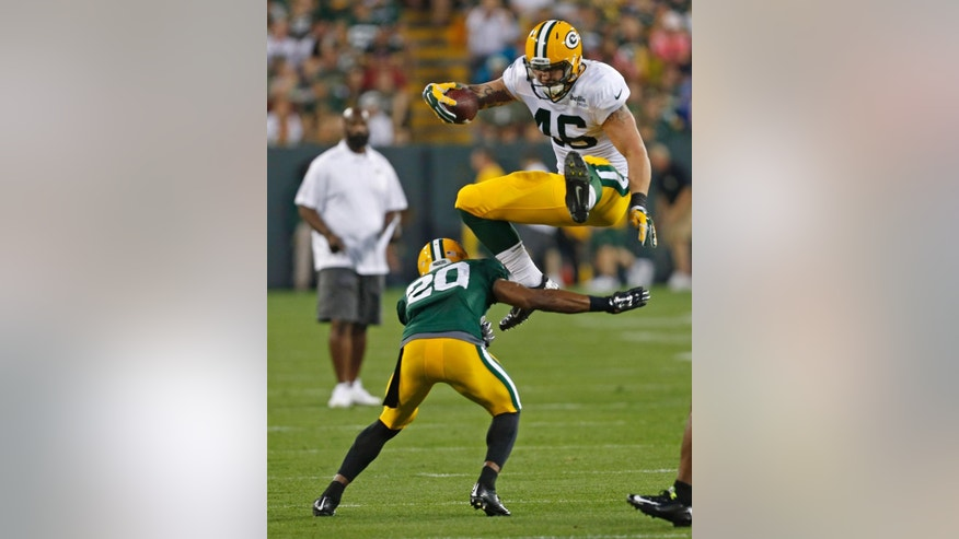 Green Bay Packers tight end Colt Lyerla jumps over defensive back Jumal Rolle during the Family Night practice of NFL football training camp Saturday, Aug. 2, 2014, in Green Bay, Wis. (AP Photo/Matt Ludtke)